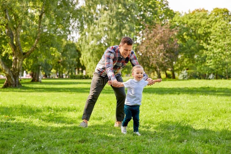 Glad far med son som leker i sommarparken arkivfoton