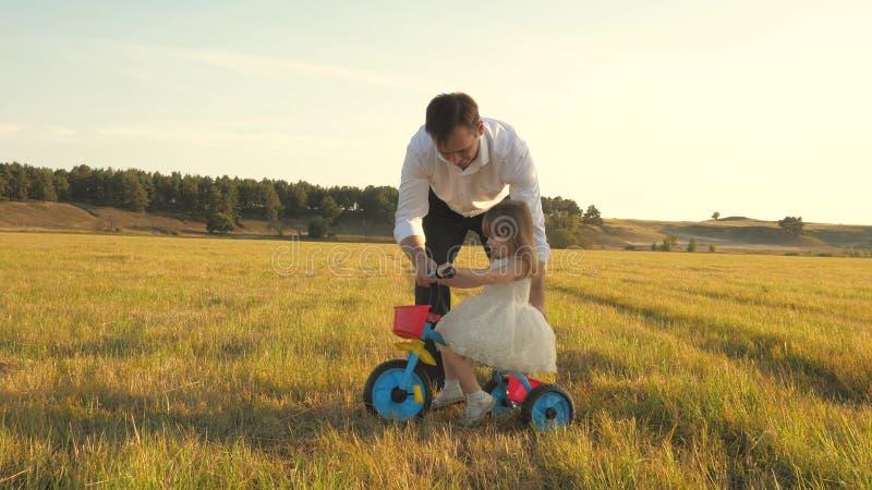 Glad far undervisar liten dotter att cykla Pappa leker med ett litet barn på gräset barn lär sig att cykla arkivbilder