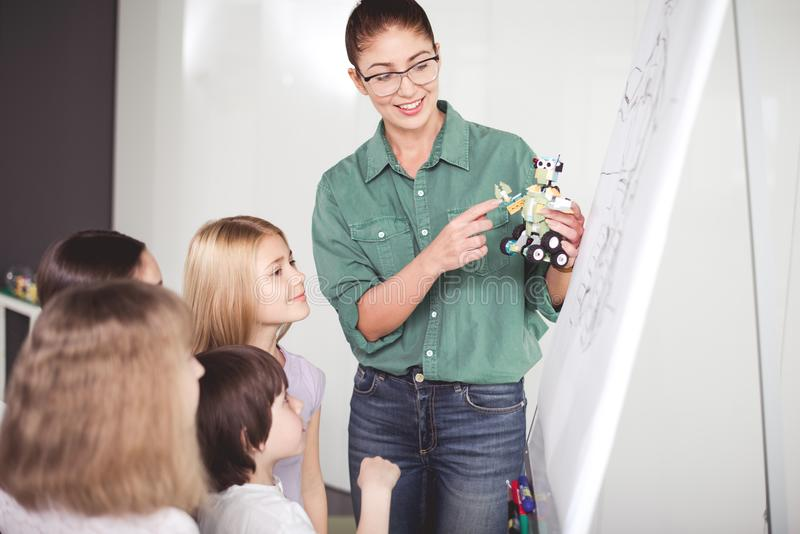 Glad female conducting study about technological toy stock photo