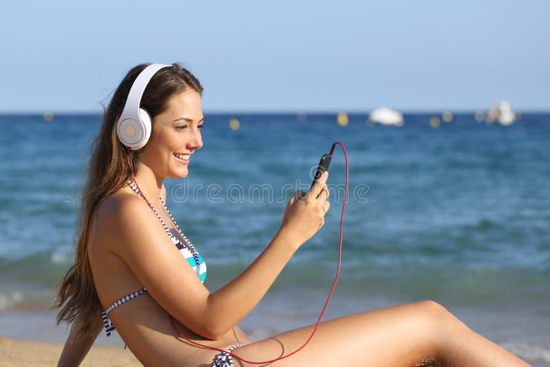 Glad flicka i bikini som lyssnar på musik med telefon på stranden arkivbild