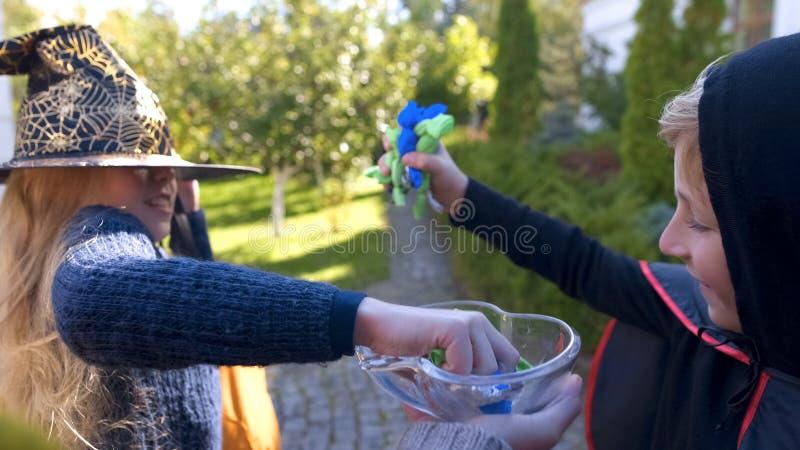 Glad flicka och pojke som tar alla gränsa till godisar som trick-eller-behandlar på allhelgonaafton royaltyfri bild