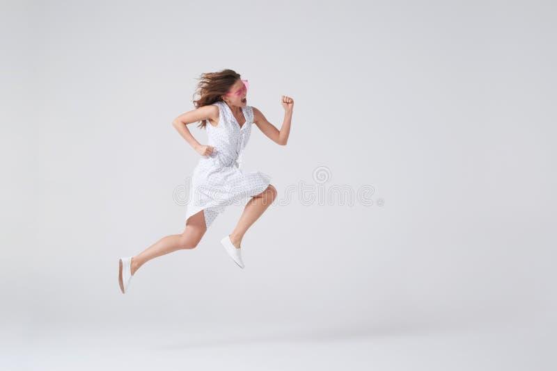 Glad flicka som hoppar upp i luft över bakgrund i studio royaltyfria bilder