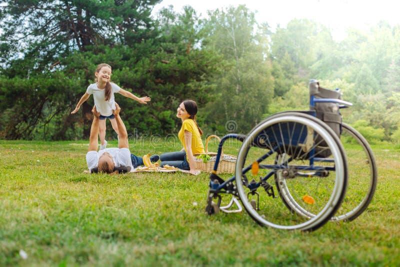 Glad flicka som spelar med henne den rörelsehindrade farsan som ligger på gräs royaltyfri fotografi