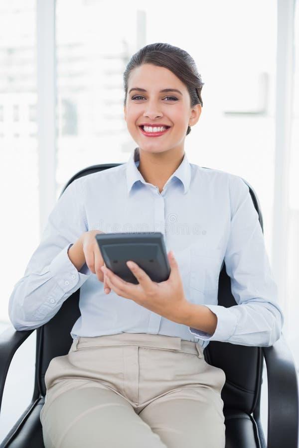 Glad flott brun haired affärskvinna som använder en räknemaskin royaltyfria foton