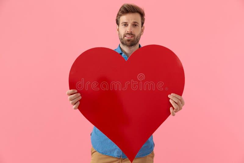 Glad fritidskille som ler och håller ett stort rött hjärta arkivfoton