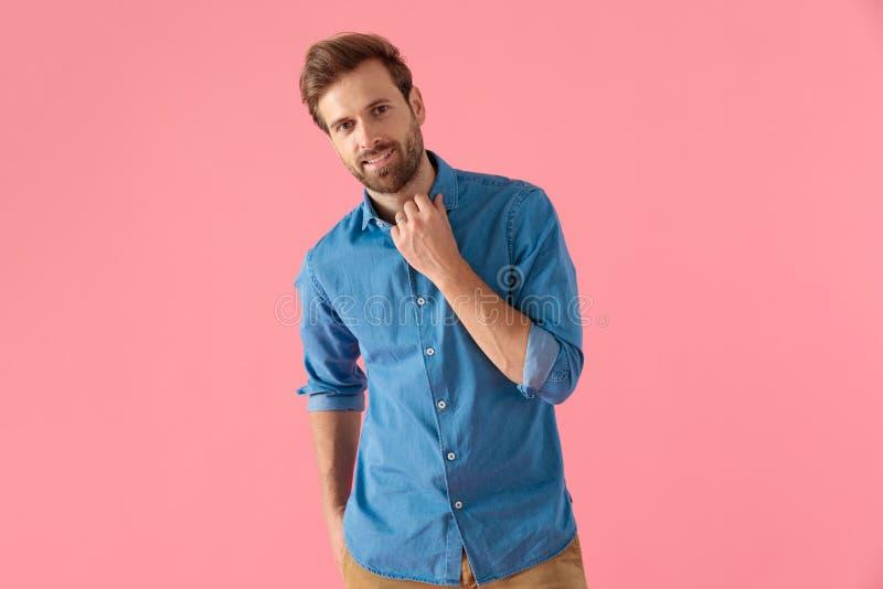 Glad fritidsman i denim-skjortan som fixerar krage och ler royaltyfri foto