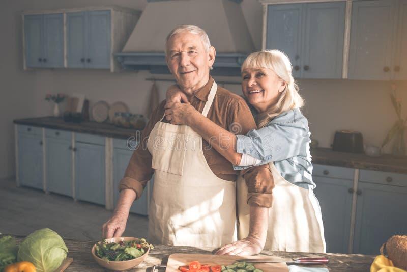 Glad fru som kramar hennes make i kockrum royaltyfri foto
