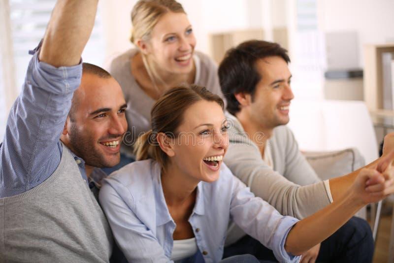 Glad grupp av vänner som håller ögonen på fotbollleken royaltyfri bild