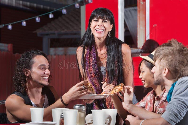 Glad grupp som delar pizza royaltyfria foton