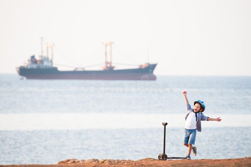 Glad gullig liten unge med sparkcykeln på havskusten med ett seglingskepp royaltyfria bilder