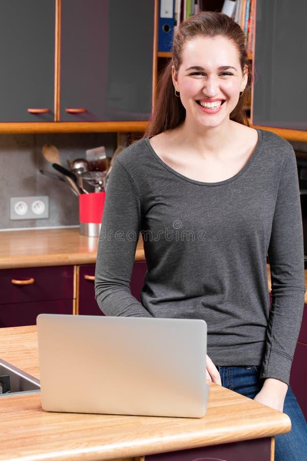 Glad härlig ung kvinna med bärbara datorn i kök för telecommuting arkivfoto
