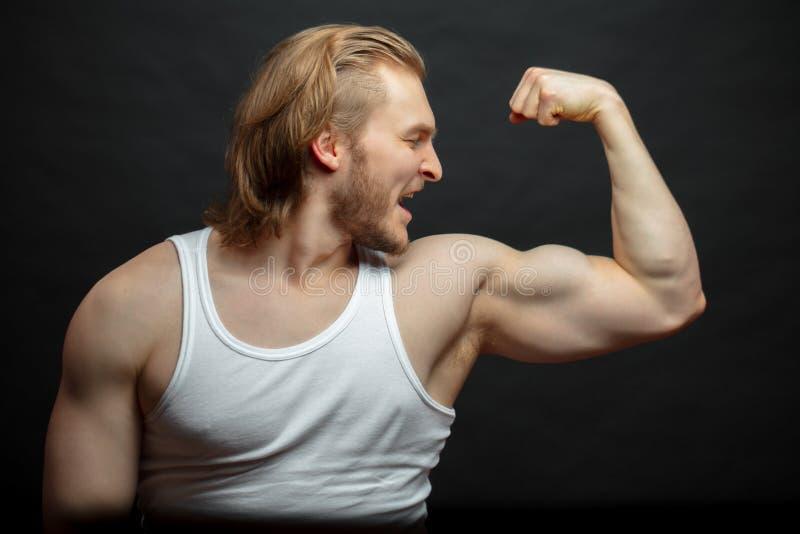 Glad idrottsman nen som beundrar med hans starka armar som isoleras på den svarta bakgrunden arkivbilder