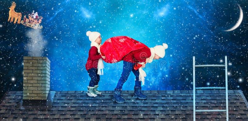 Glad jul! Barn bär en påse av gåvor från jultomten Jultomten tappade en säck av gåvor till småbarn på taket av ho arkivbild