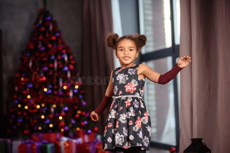 Glad jul! Den gulliga flickan f?r det lilla barnet dekorerar julgranen royaltyfria foton