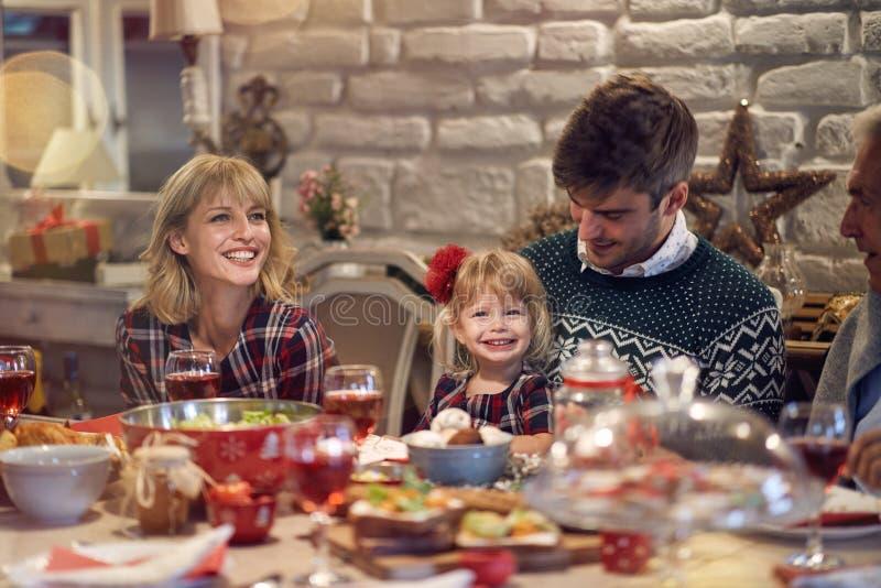 Glad jul! familjen har matställen hemma Berömferie och samhörighetskänsla royaltyfri fotografi