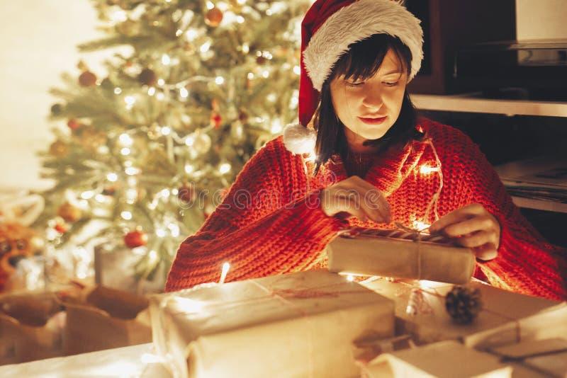 glad jul flicka som slår in julgåvor i ljus i e arkivfoton