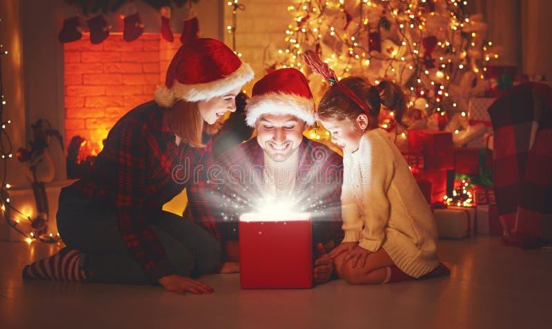 Glad jul! lycklig familjmoderfader och barn med magi royaltyfria foton