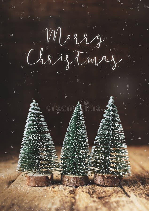 Glad jul med xmas-trädet och snö som faller på grungeträ t arkivbild