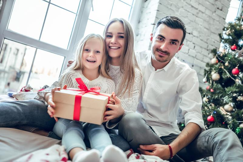 Glad jul och lyckliga ferier! Familjhopsamling runt om en julgran som rymmer en gåva arkivbild