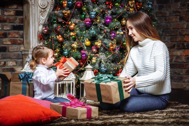Glad jul och lyckliga ferier! Gladlynt mamma och hennes gullig dotter som utbyter gåvor Förälder och litet barn som har roligt ne arkivbilder