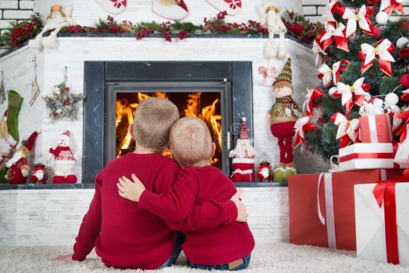 Glad jul och lyckliga ferier! Två bröder som sitter på golvet i vardagsrummet och blicken på branden i spisen I a royaltyfri foto