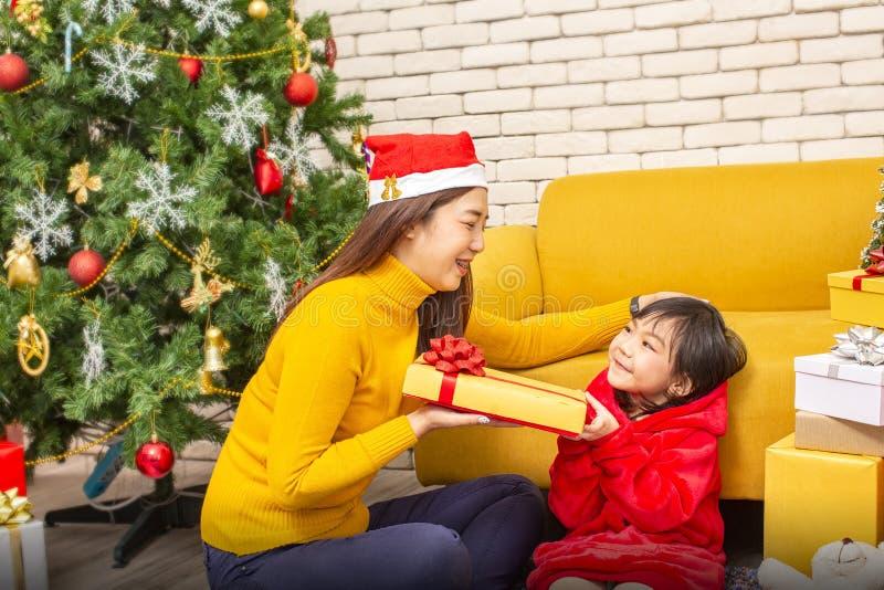 Glad jul och lyckligt lycklig nytt år för ferier eller Mamman ger gåvor till barn Den gulliga flickan ger hans älskade moder en g royaltyfri fotografi