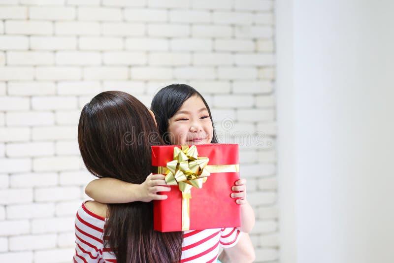 Glad jul och lyckligt lycklig nytt ?r f?r ferier eller Mamman ger g?vor till barn Den gulliga flickan ger hans ?lskade moder en g arkivfoto
