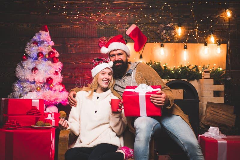 Glad jul och lyckligt nytt år Den gulliga unga kvinnan och den stiliga mannen med jultomten klär Positiv mänsklig sinnesrörelsean arkivfoto