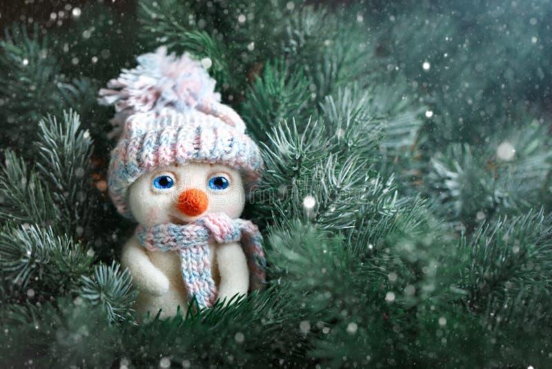Glad jul och lyckligt nytt år Ett litet leksaksnögubbeanseende i filialerna av granen Bakgrund med kopieringsutrymme arkivfoton