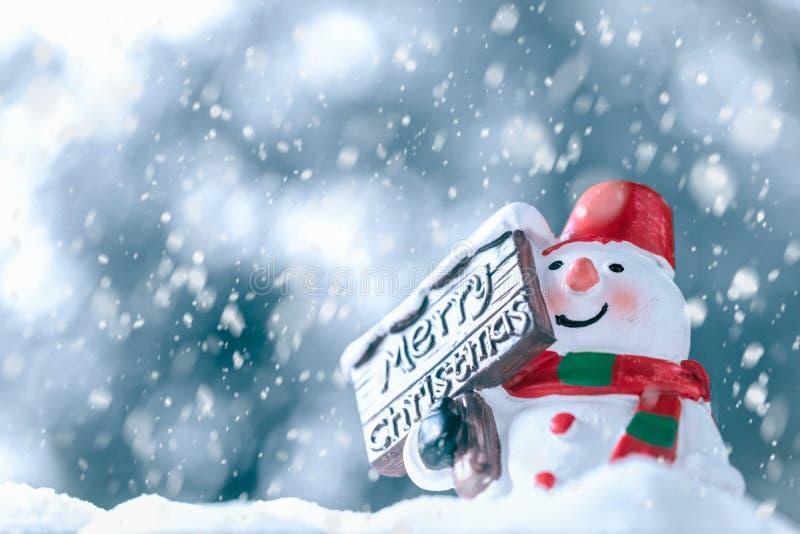 Glad jul och lyckligt nytt år, snögubbe med snönedgången, happ arkivfoton