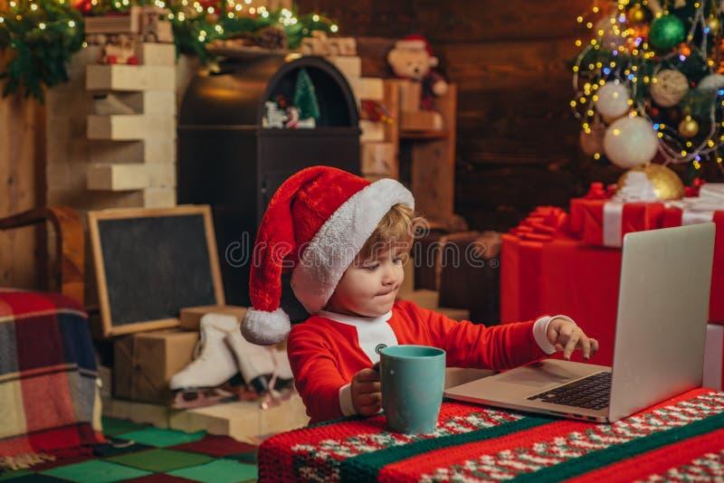 Glad jul och lyckligt nytt ?r Barnet Santa Claus använder en bärbar dator på hans seminarium Julgåvor med e-kommers arkivbilder