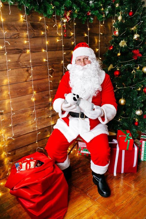 glad jul Santa Claus nära julgranen med gåvor arkivbilder