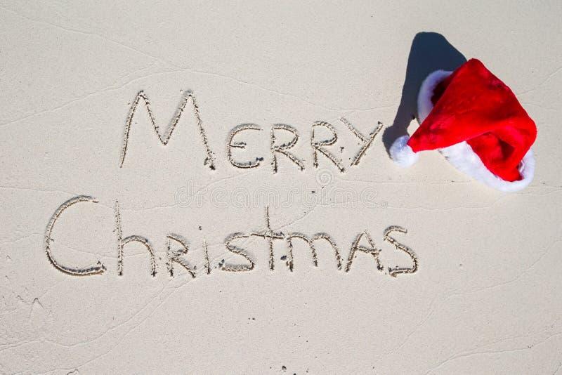 Glad jul som är skriftlig på tropisk strandvit royaltyfri foto
