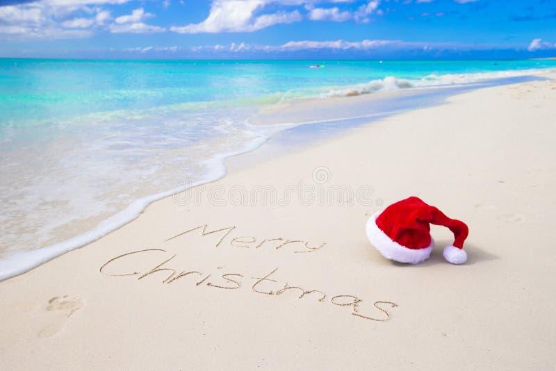Glad jul som är skriftlig på vit sand för strand med arkivbilder