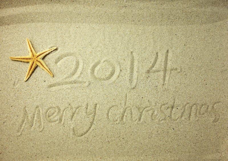 Glad jul som är skriftlig på vit sand för tropisk strand royaltyfri bild