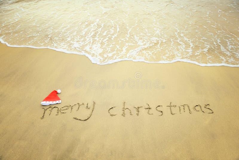 Glad jul som är skriftlig på vit sand för tropisk strand royaltyfri fotografi