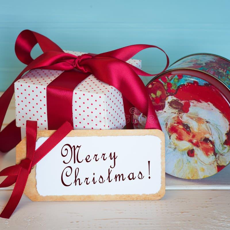 Glad julkort med en tappning Santa Candy Tin och röd och vit gåvagåva som binds med en röd satängpilbåge och en etikett med Holid royaltyfria bilder