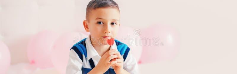 Glad kaukasisk, penetrerande barnpojke som äter hjärtform röd lollipop-godis Alla hjärtans dag kärlekssemesterkoncept Webbbandero royaltyfria bilder