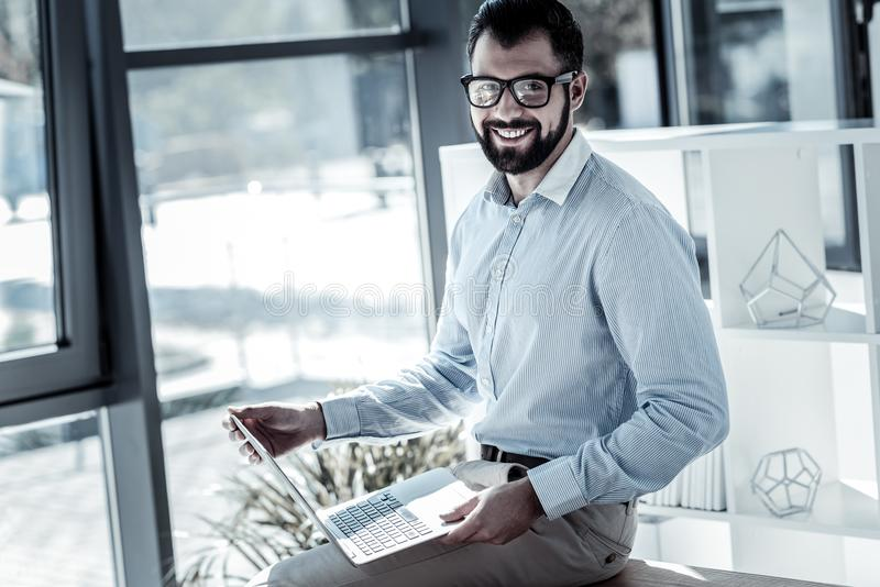 Glad kvalificerad arbetare som rymmer bärbara datorn och le arkivfoton