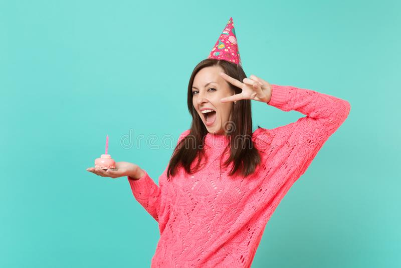 Glad kvinna i den stack rosa tröjafödelsedaghatten som håller det breda öppna visande segertecknet för mun, håll i handkaka med royaltyfri foto