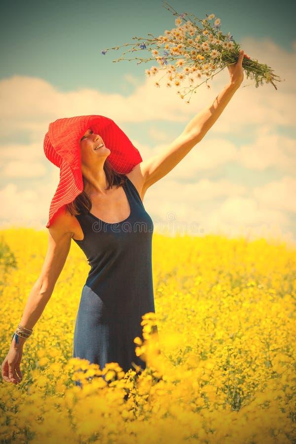 Glad kvinna i en röd hatt med en bukett av lösa blommor arkivbild