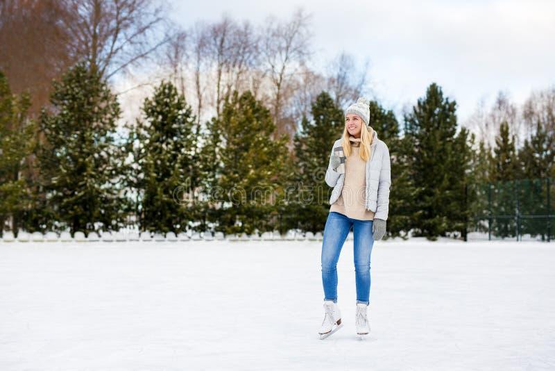 Glad kvinna i isskiffer som pockar med en kaffekopp på rink i vinterparken - kopiera utrymme över is fotografering för bildbyråer
