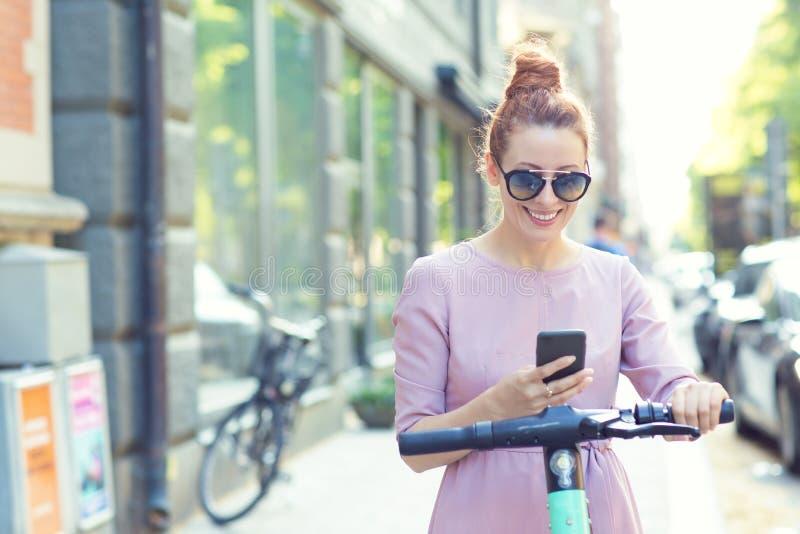 Glad kvinna i solglasögon som använder smartphone och hyr moderna elskotrar med ett program arkivbild