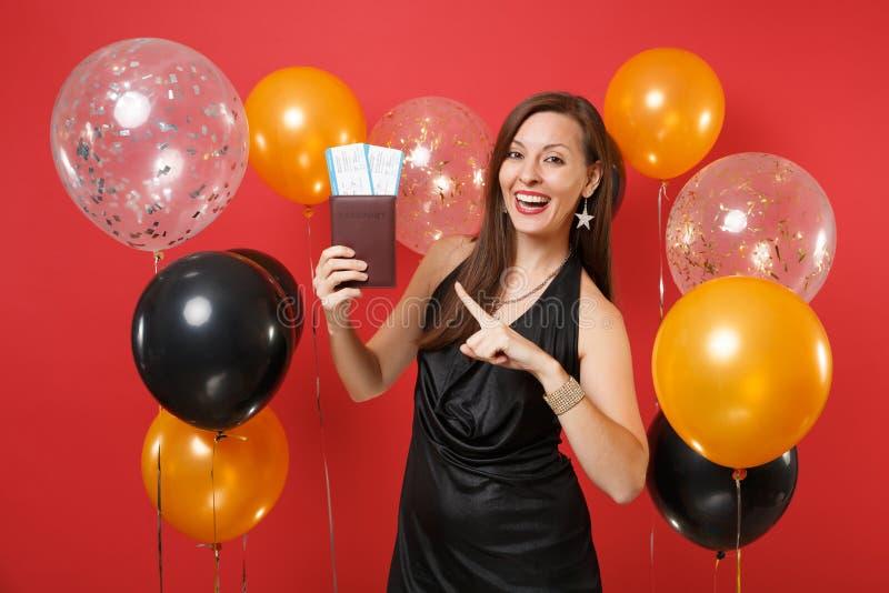 Glad kvinna i svart fira för klänning som pekar pekfingret på pass, biljetter för logipasserande i hand på ljust rött arkivbild