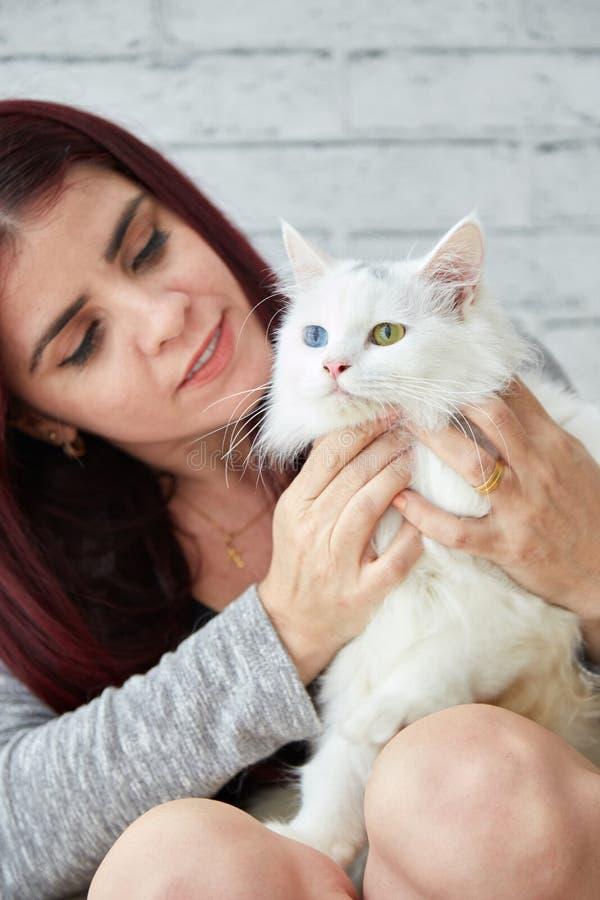 Glad kvinna med den vita katten arkivfoto