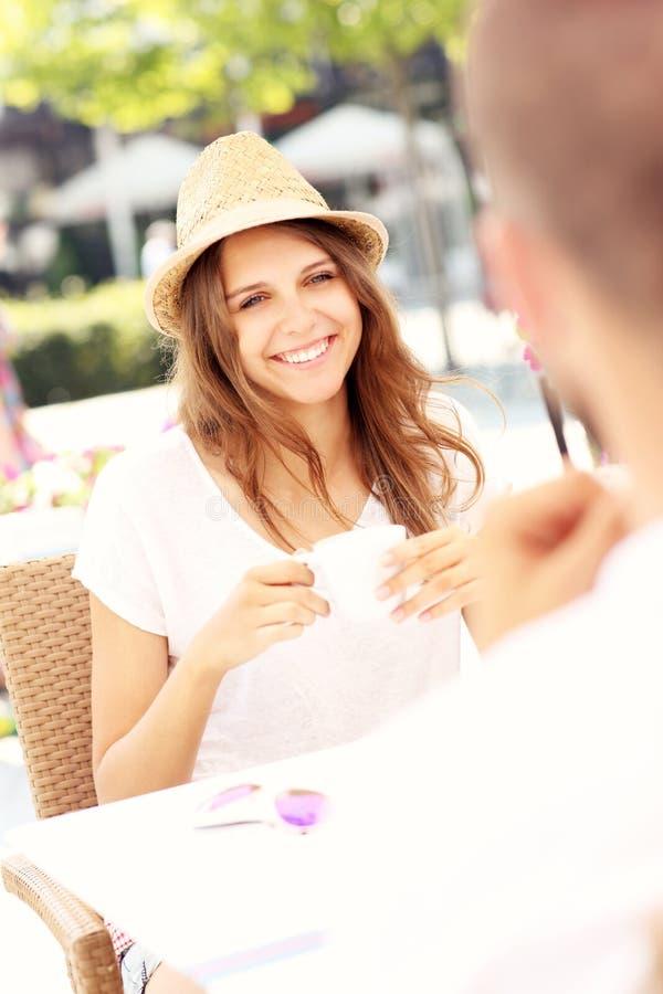 Glad kvinna på ett datum i kafé arkivfoto