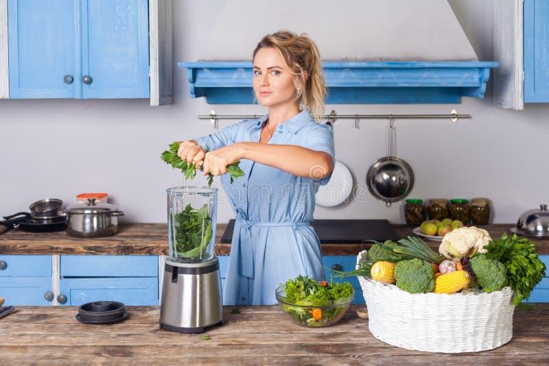 Glad kvinna som blandar ihop ingredienser för att göra frukost friska, koka grönsaker som bereder sallad royaltyfri bild
