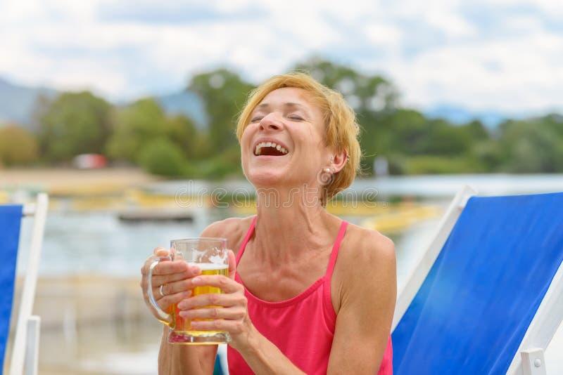 Glad kvinna som dricker öl som ut högt skrattar royaltyfri bild