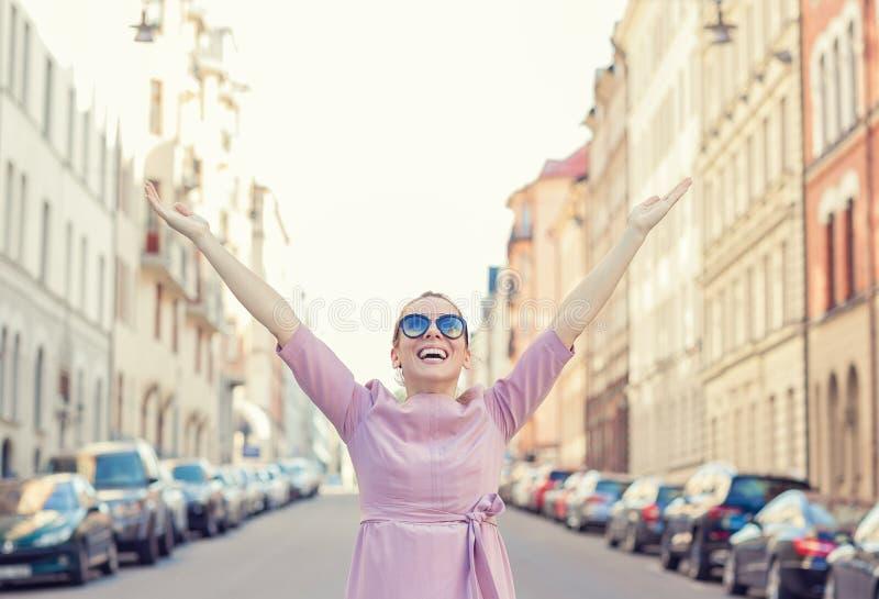 Glad kvinna som känner sig fri med vapen som är öppna i stadens bakljus royaltyfri bild