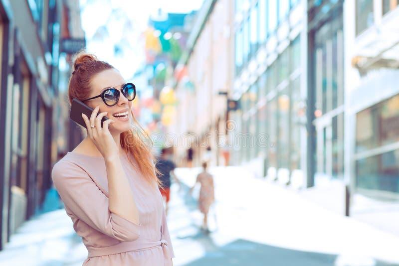 Glad kvinna som ringer på en mobiltelefon som ser bort från gatan royaltyfri bild